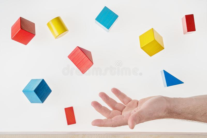 Male hand juggling colorful wooden shapes. Concept of creative, logical thinking. Floating shapes stock photo