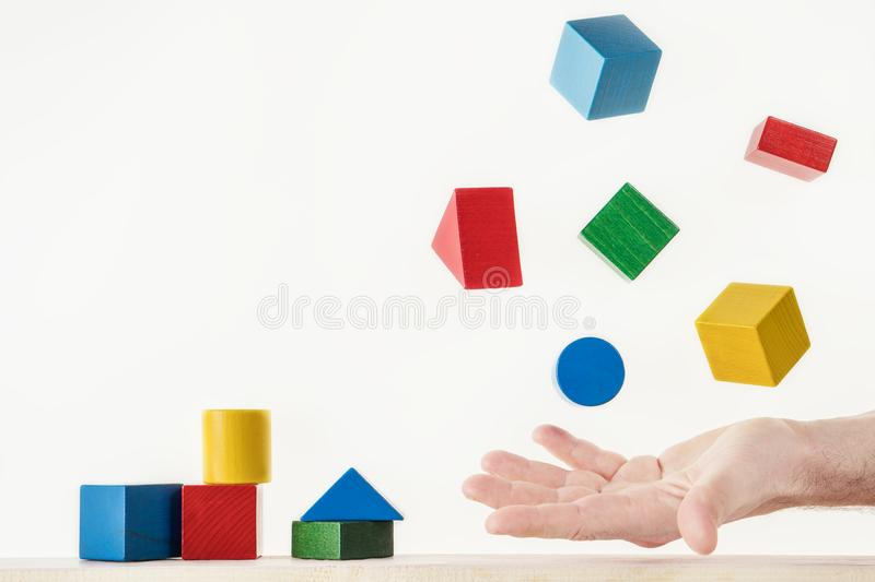 Male hand juggling colorful wooden shapes. Concept of creative, logical thinking. Floating shapes royalty free stock photos
