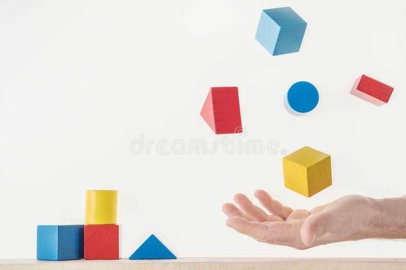 Male hand juggling colorful wooden shapes. Concept of creative, logical thinking. Floating shapes stock photos
