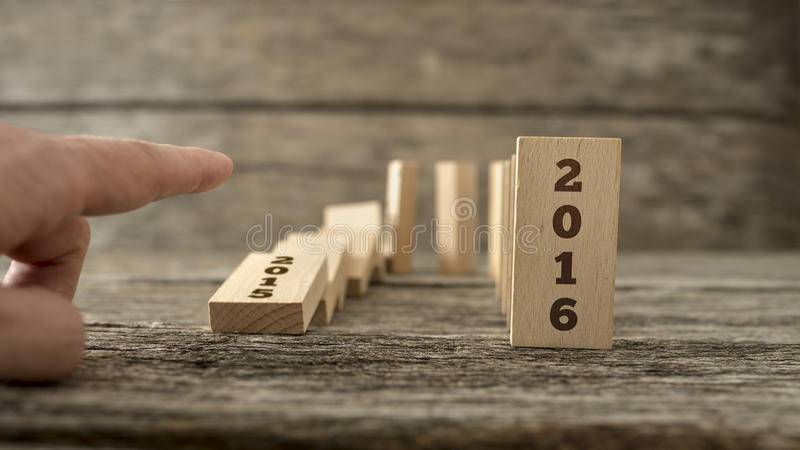 Male hand knocking down a line of domino with the first one hold. Male hand knocking down a U shaped curve of domino with the first one holding a sign 2015 and royalty free stock photos