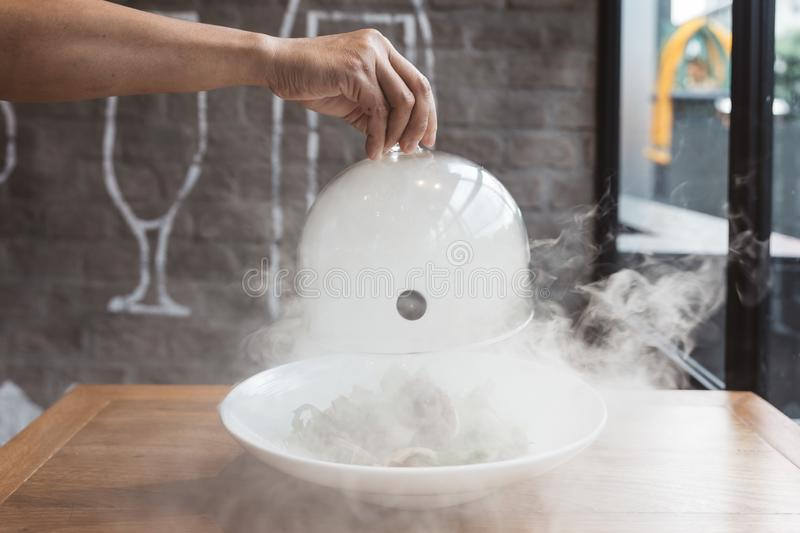 Male hand lifts to up glass cloche from a plate with hot food and moving smoke at the restaurant - Smoked food time! Close Up royalty free stock images