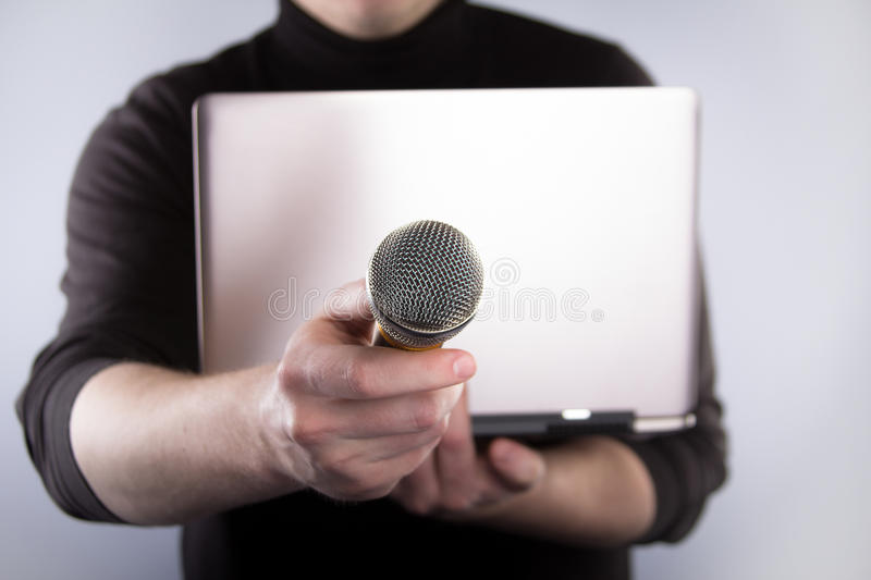 Male hand with microphone and notebook
