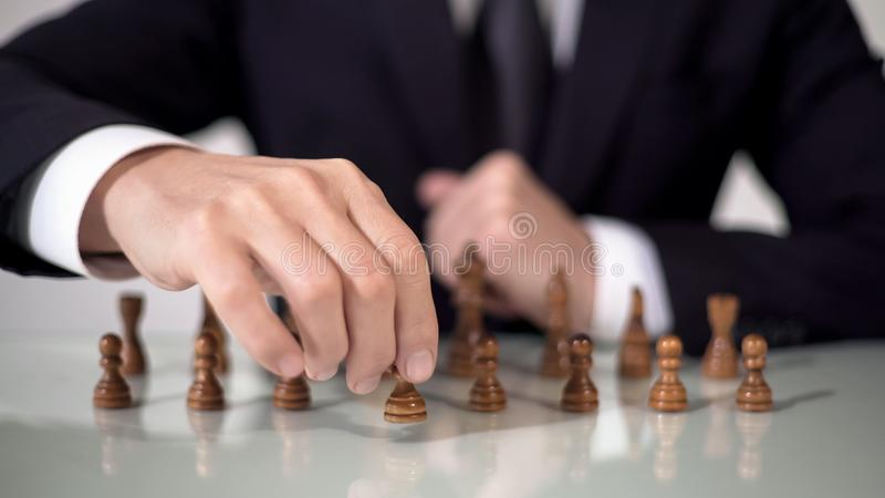 Male hand moving pawn in chess game, strategic start for successful project royalty free stock photos