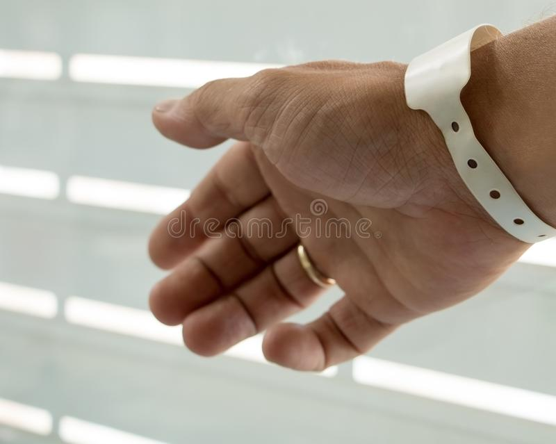 Male hand with newborn birth tag stock image