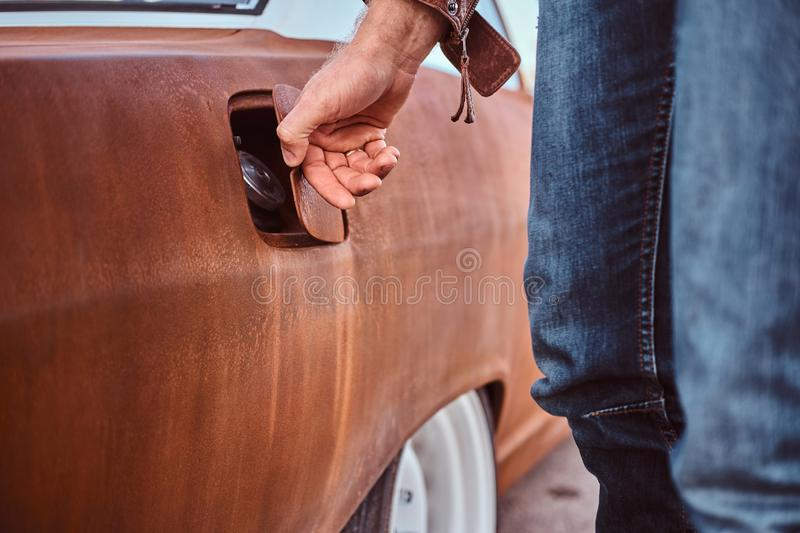 Male hand opens the gas cap of a tuned retro car for refueling. royalty free stock photography