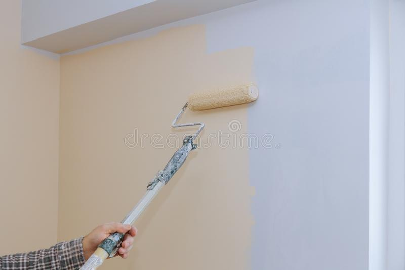 Male hand painting wall with paint roller. Painting apartment, renovating with color paint. Male hand painting wall with paint roller apartment, renovating with stock photos