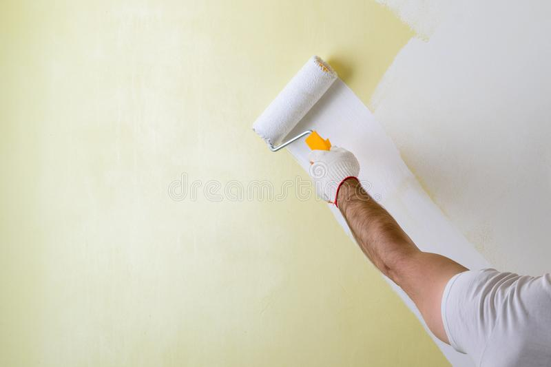 Male hand painting wall with paint roller. Painting new apartment renovating with yellow color paint royalty free stock photo