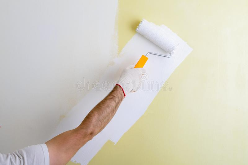 Male hand painting wall with paint roller. Painting new apartment renovating with yellow color paint stock photo