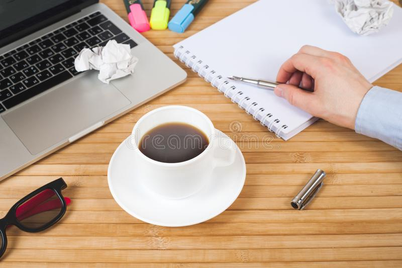 Male hand with pen on notebook, coffee cup, pen, markers, glasses and laptop on wooden table. Work space in office. Business,. Education, people and technology royalty free stock image