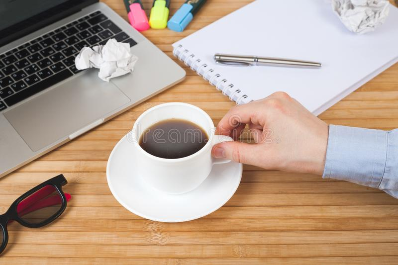 Male hand with pen on notebook, coffee cup, pen, markers, glasses and laptop on wooden table. Work space in office. Business,. Education, people and technology stock photo