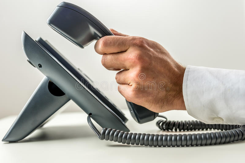 Male hand picking up the receiver of a telephone. Close-up of a male hand with white sleeve shirt picking up the receiver of a black landline office telephone royalty free stock image