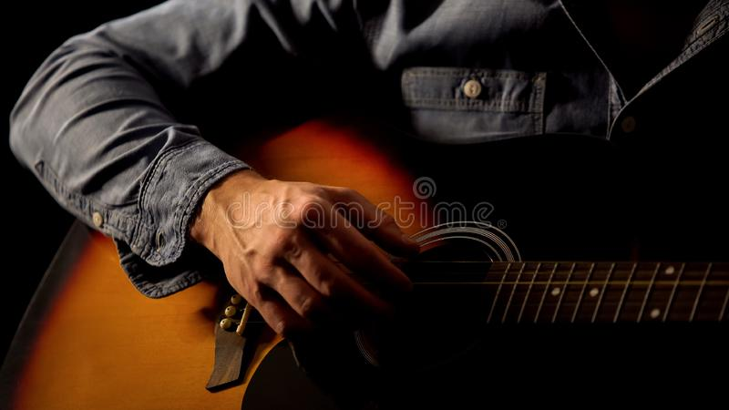 Male hand playing acoustic guitar close up, street artist earning for living. Stock photo royalty free stock photo