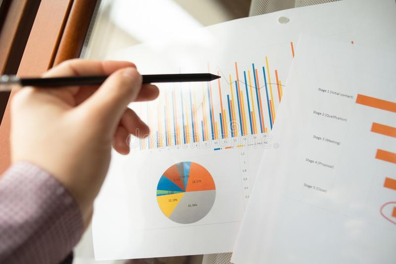 Male hand pointing at charts printed on a white sheet of paper during a business meeting stock photography