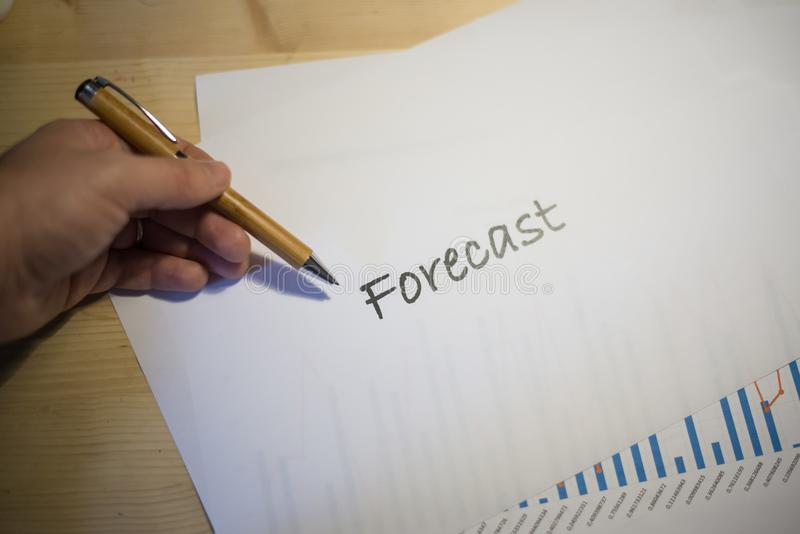 Male hand pointing at a Forecast document printed on a white sheet of paper during a business meeting royalty free stock photography