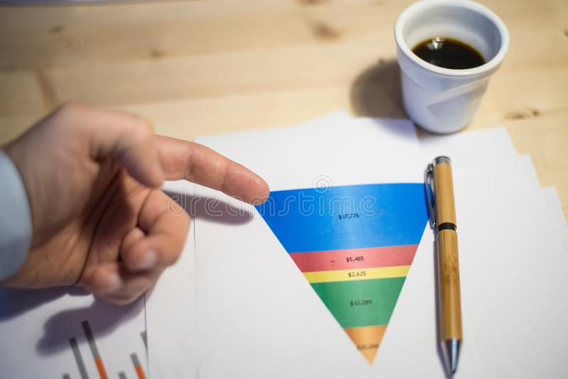 Male hand pointing at a sales funnel printed on a white sheet of paper during a business meeting stock image