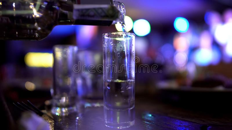 Male hand pouring in huge shot of vodka, alcoholism issues, failed abstinence. Stock photo stock photos