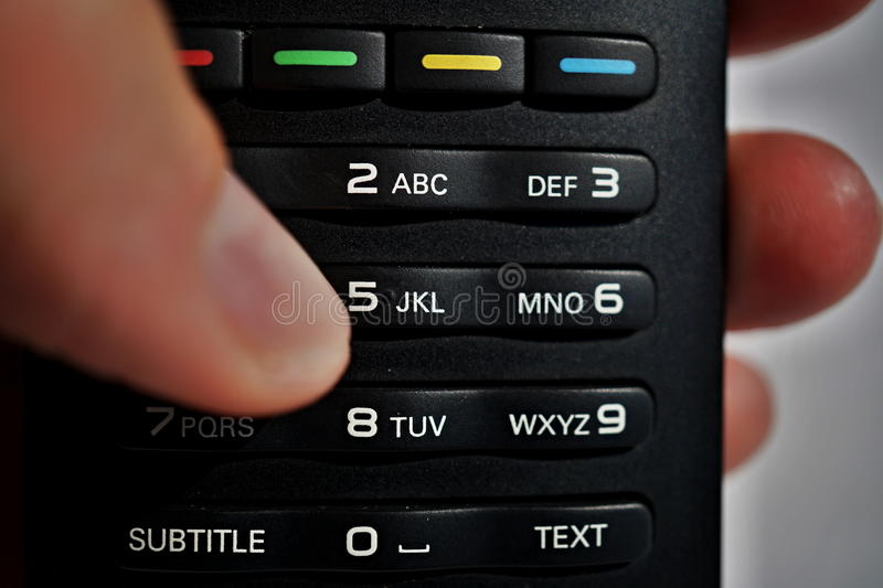 Male hand pressing numerical keyboard in the remote control as symbol of choice and home entertainment when watching television stock photography
