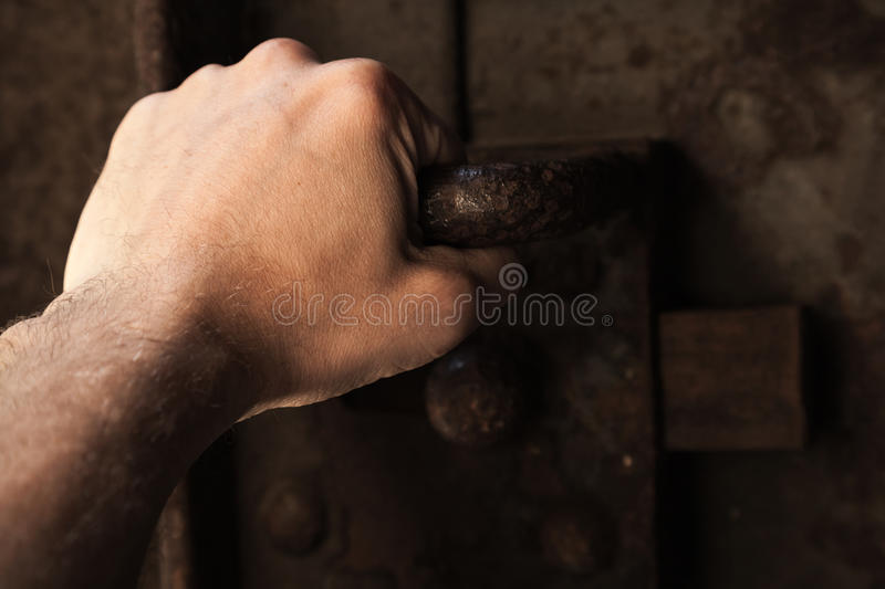 Male hand pull the handle of old rusted metal door. Male hand pull the handle of old rusted prison metal door with big lock royalty free stock photo