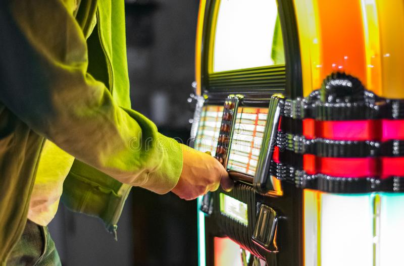 Male hand pushing buttons to play song on old Jukebox stock photo