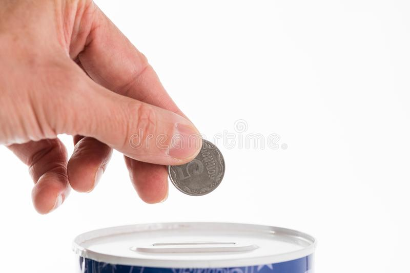Male hand putting a coin into tin can saving bank royalty free stock images