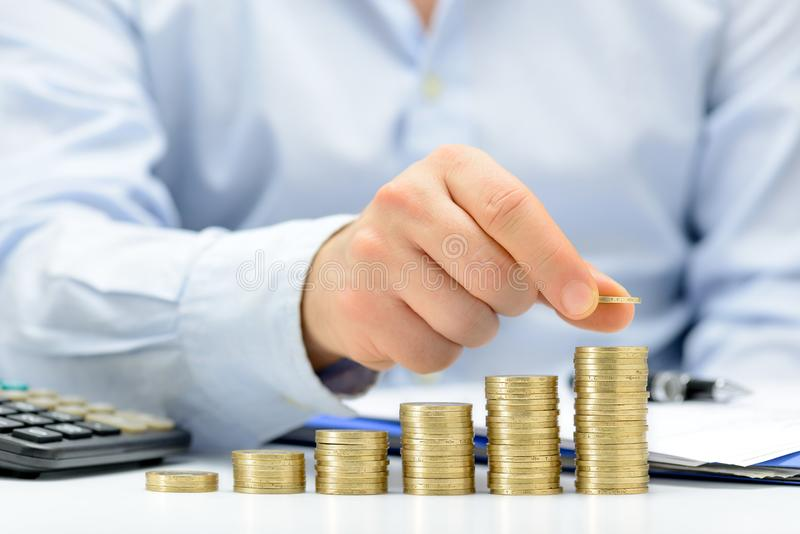 Male hand putting money coin stack growing business. royalty free stock photography
