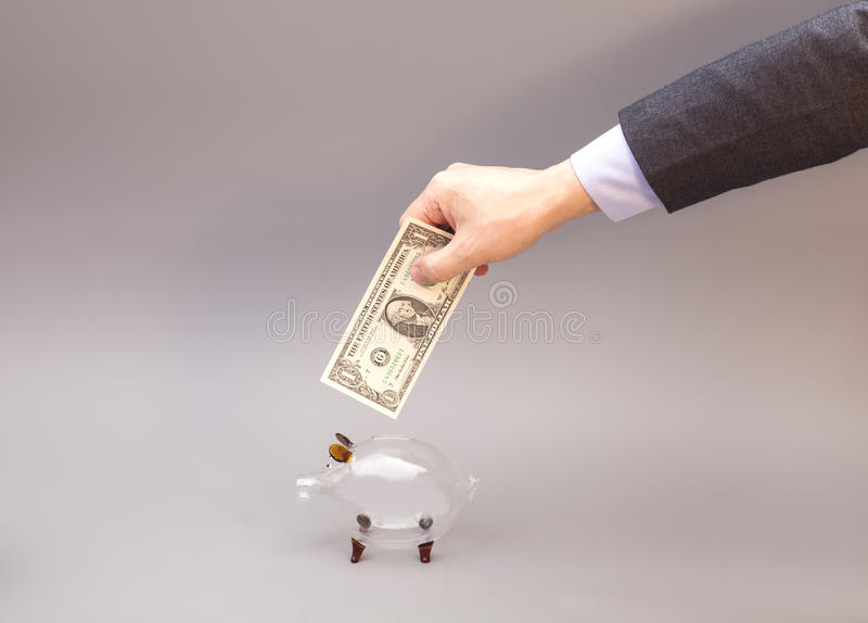 Male hand putting one dollar bill into glass piggy bank stock image