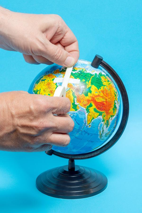 Male hand putting a patch on a globe. Sign, ecology, natural, element, ecological, environment, green, symbol, world, nature, earth, protection, map, concept stock images