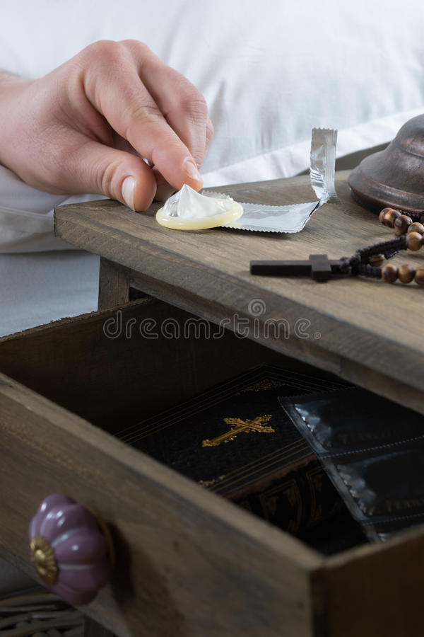 Male hand reaches a condom from a bedside table royalty free stock photo