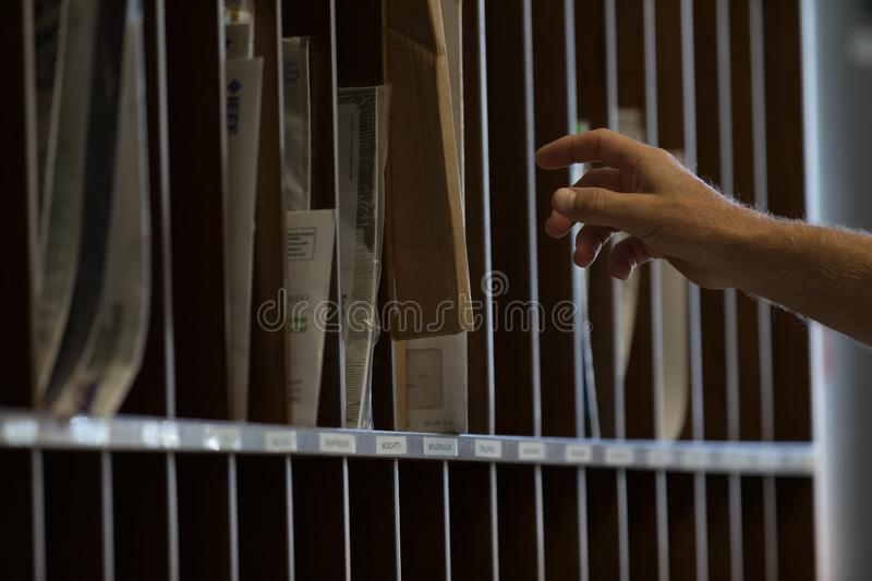 Male hand reaching for sorted post or mail stock photography