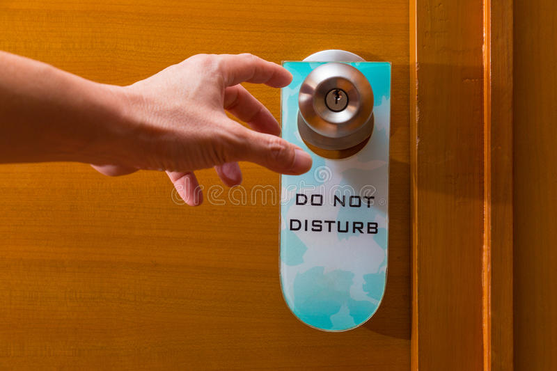 Male hand reaching to door knob with Do Not Disturb sign haning stock photography