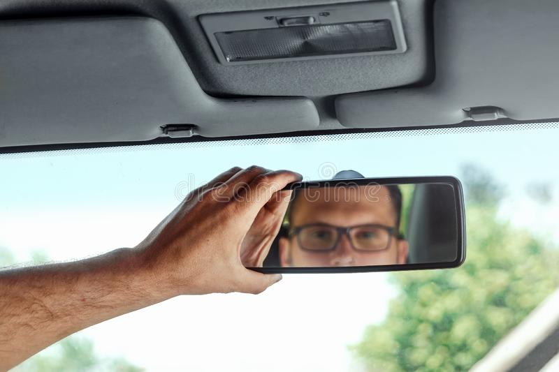 Male hand on the rearview mirror of a car, close-up. Manual adjustment of a rear-view mirror.  stock photos