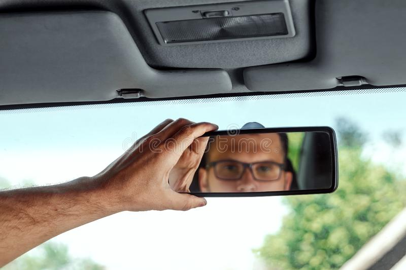 Male hand on the rearview mirror of a car, close-up. Manual adjustment of a rear-view mirror.  stock photo