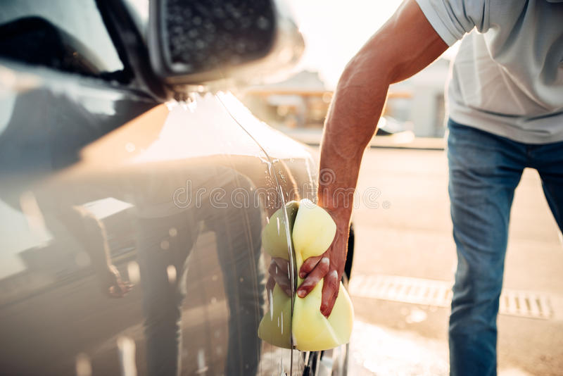 Male hand rubbing the car with foam, carwash stock photo
