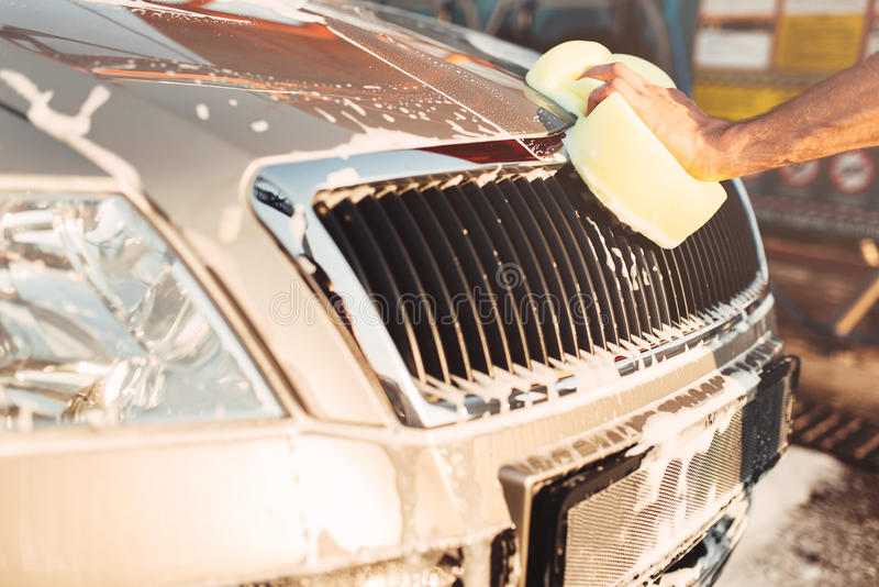 Male hand rubbing the car with foam, carwash. Male hand rubbing the car with foam, automobile in suds. Carwash station royalty free stock photos