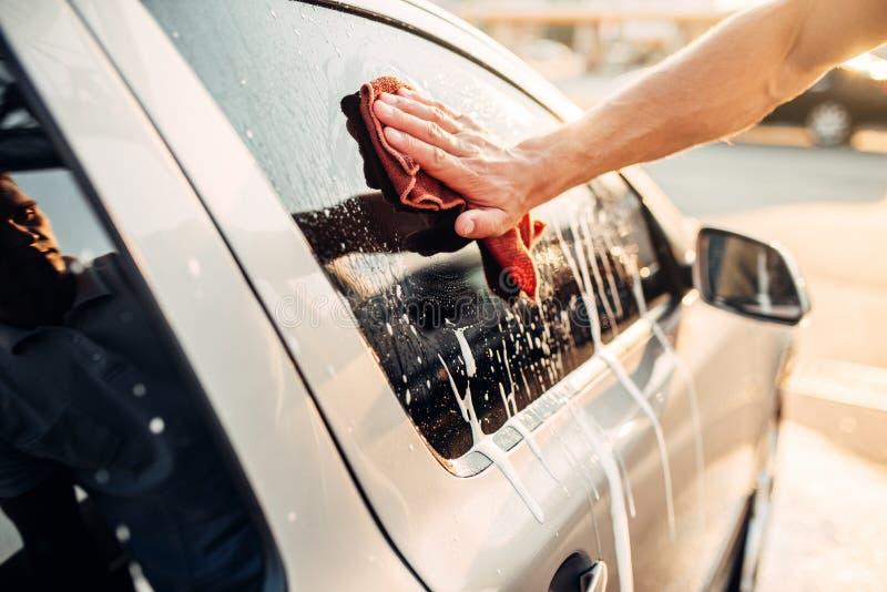 Male hand rubbing car window with foam, carwash. Male hand rubbing vehicle window with foam, automobile in suds, car wash. Carwash station royalty free stock image