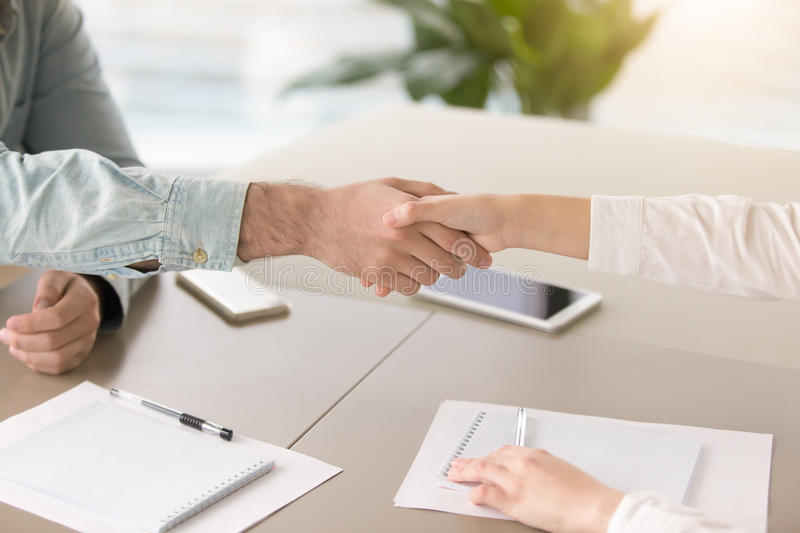 Male hand shaking hand of young female over office desk royalty free stock images