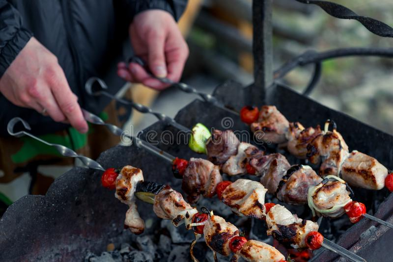 Male hand with shish kebab skewers on the grill stock photography