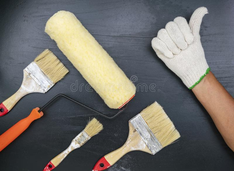 Male hand showing thumbs up with paint brush on black background stock images