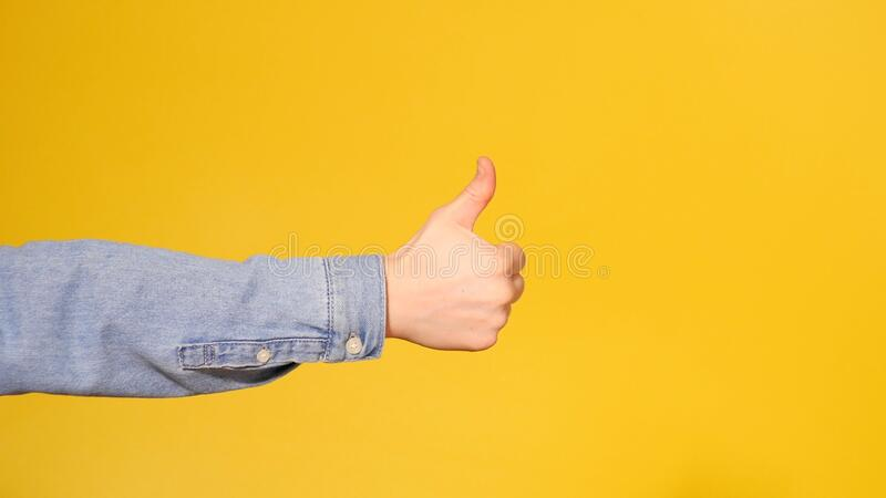 Male Hand Showing Thumbs Up Sign. Yellow background. Copy space stock photos
