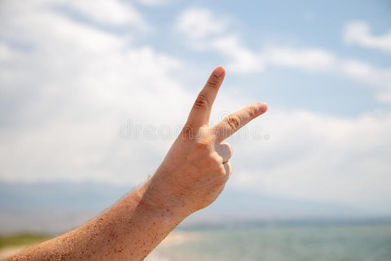 Male hand shows 2 fingers or victory sign. Against the sky and the sea. Rest and relaxation stock images