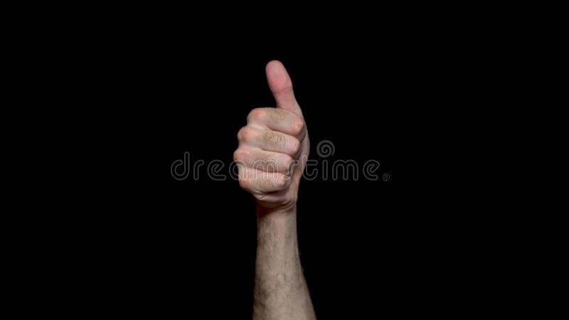 Male hand shows good job sign, thumbs up for agreement, success business concept. Isolated on black background, hand royalty free stock photo