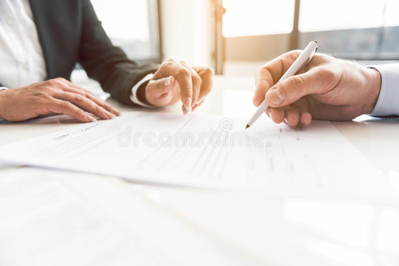 Male hand signing contract at desk stock photo