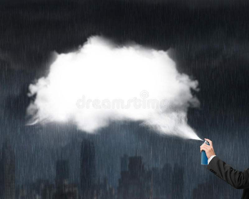 Male hand spraying white cloud on heavy rain dark cityscape stock images