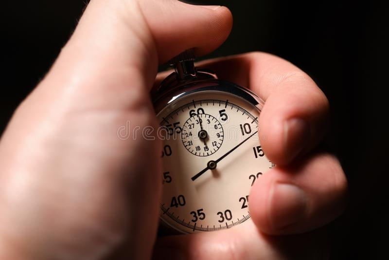 Male hand starts the analog stopwatch on a black background, close-up, isolate stock image