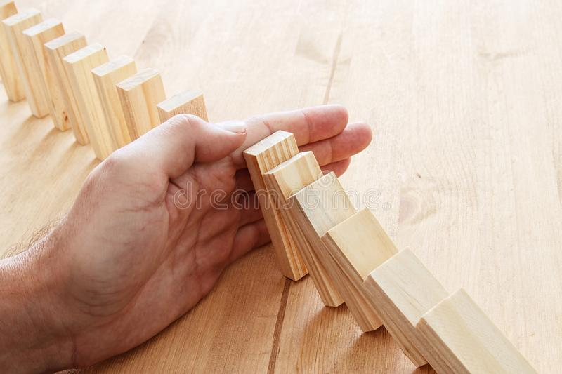 a male hand stopping the domino effect. retro style image executive and risk control concept. royalty free stock photo