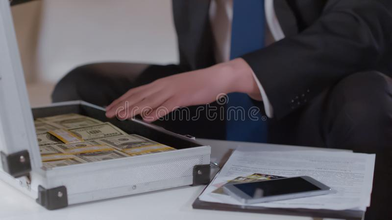 Male hand in suit checking money in case, kickback for secret business agreement royalty free stock images