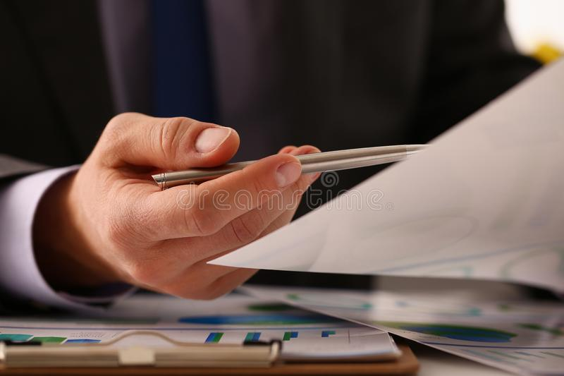 Male hand in suit hold siver pen in office. With clipboard on table closeup. Comprehensive audit of enterprise business at all stages development stock photo