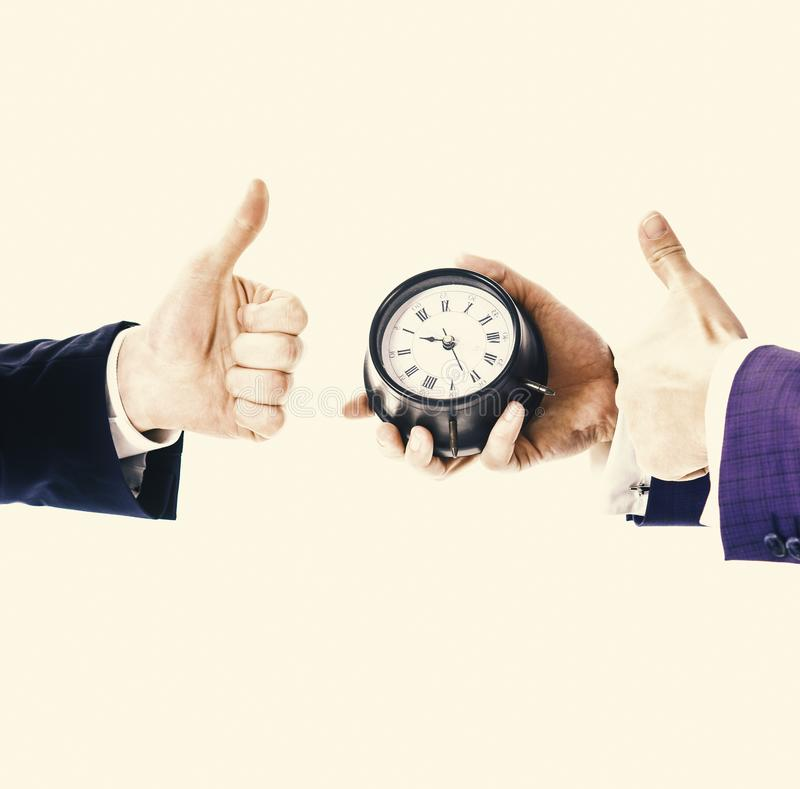 Male hand in suit holds clock, copy space. Time management. royalty free stock images
