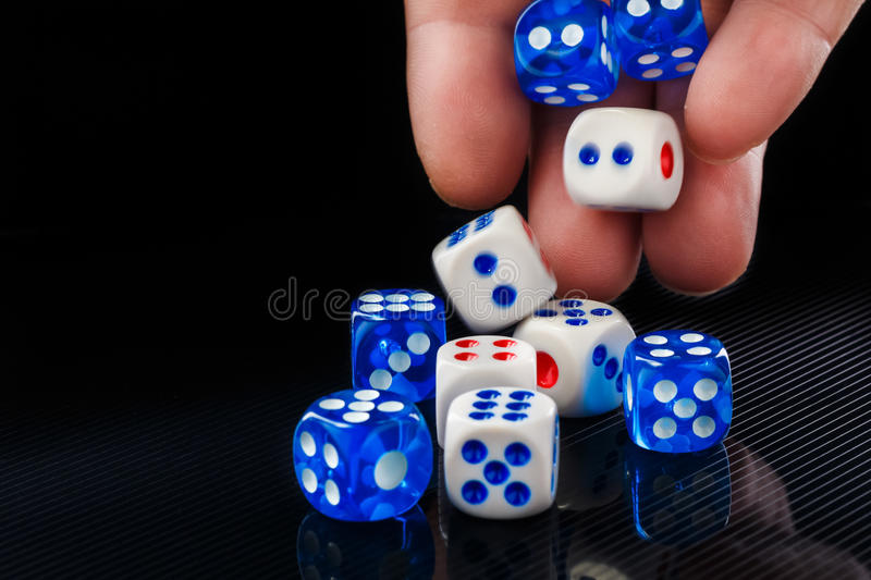 The male hand throwing dices on dark background royalty free stock photo