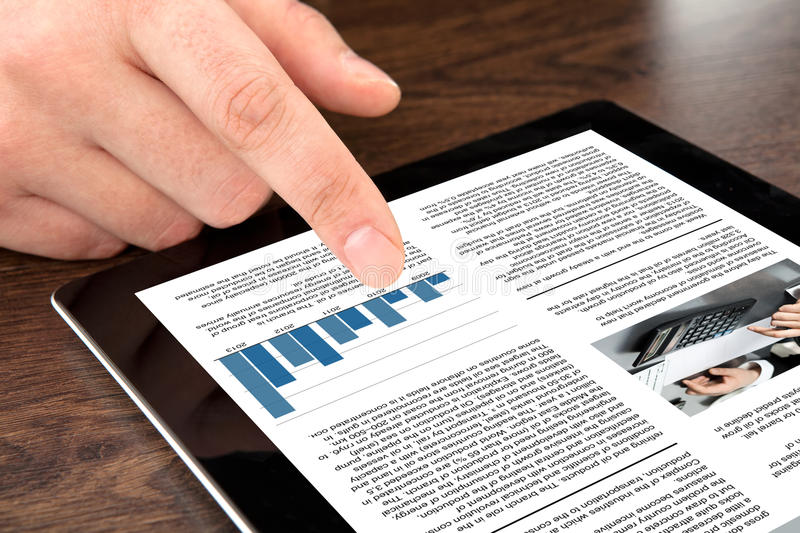 Male hand touching tablet with business news on screen royalty free stock image